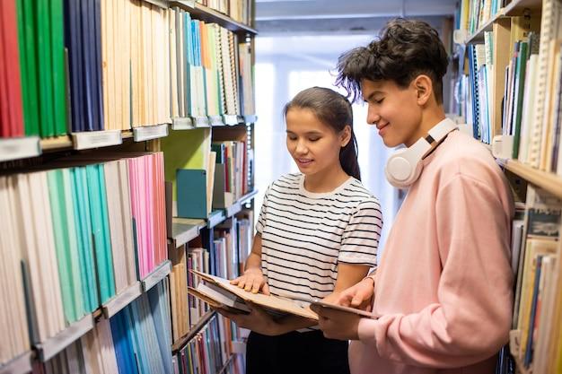 Studente di college con tablet e il suo compagno di classe guardando attraverso il libro in biblioteca mentre si trovava tra gli scaffali
