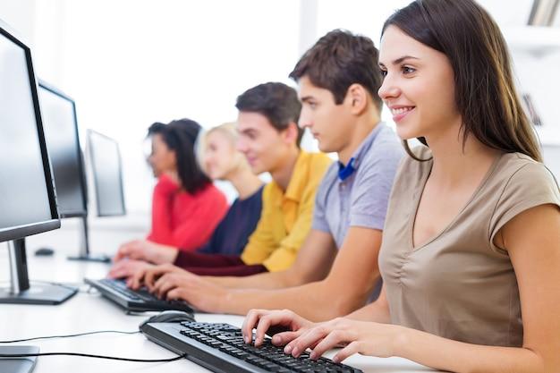 Studenti universitari seduti in classe, che utilizzano computer portatili durante la lezione (dof superficiale)