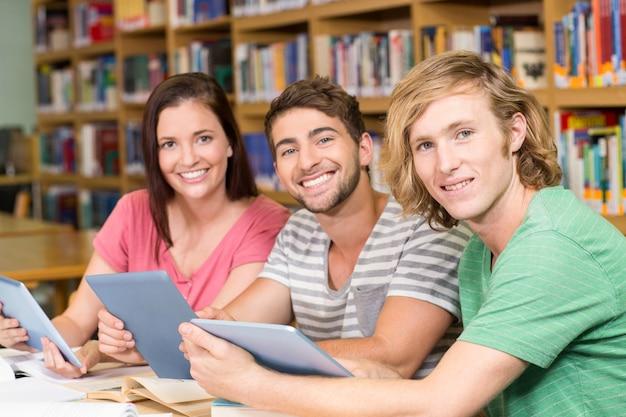 Studenti universitari utilizzando tavolette digitali in biblioteca