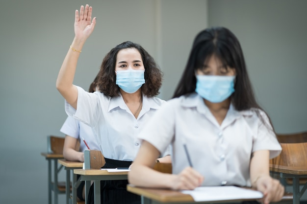 Gli studenti universitari indossano lo studio della maschera facciale in classe e alzano la mano per chiedere all'insegnante durante la pandemia di coronavirus. ritratto di messa a fuoco selettiva degli studenti universitari che studiano in classe.