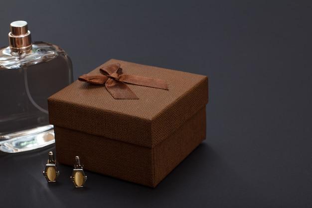 Colonia per uomo, confezione regalo marrone e gemelli su sfondo nero. accessori per uomo.