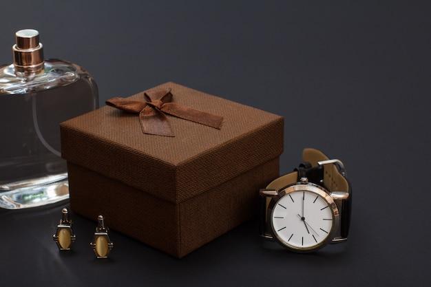 Colonia da uomo, confezione regalo marrone, gemelli e orologio con cinturino in pelle nera su sfondo nero. accessori per uomo.
