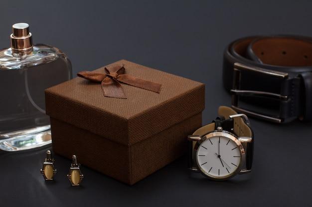 Colonia da uomo, confezione regalo marrone, gemelli, orologio con cinturino in pelle nera e cintura in pelle con fibbia in metallo su sfondo nero. accessori per uomo.
