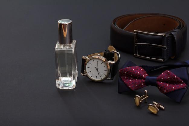 Colonia da uomo, orologio con cinturino in pelle nera, cintura in pelle con fibbia in metallo, papillon e gemelli su sfondo nero. accessori per uomo.