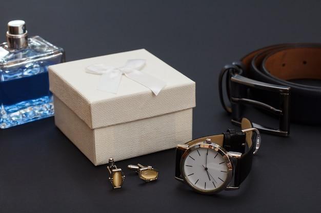 Colonia da uomo, confezione regalo bianca, gemelli, orologio con cinturino in pelle nera e cintura in pelle con fibbia in metallo su sfondo nero. accessori per uomo.