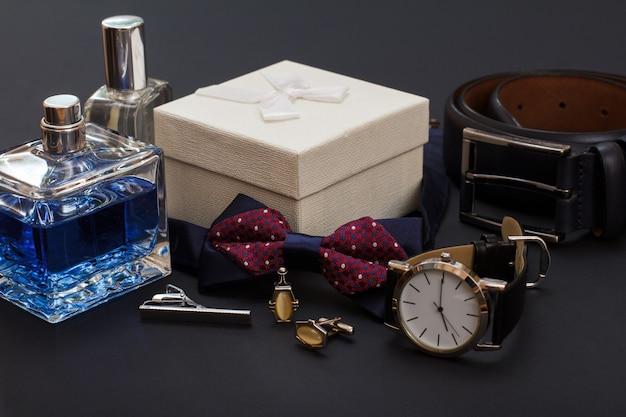 Colonia da uomo, gemelli, scatola regalo bianca, papillon, orologio con cinturino in pelle nera e cintura in pelle con fibbia in metallo su sfondo nero. accessori per uomo.
