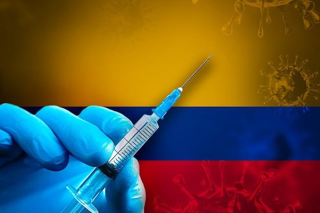 Campagna di vaccinazione della colombia covid19 la mano in un guanto di gomma blu tiene la siringa davanti alla bandiera