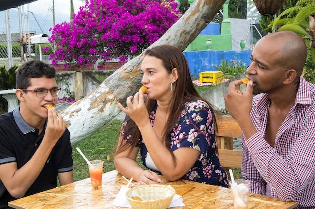 Famiglia colombiana che gode di un picnic che mangia torta e succo di frutta