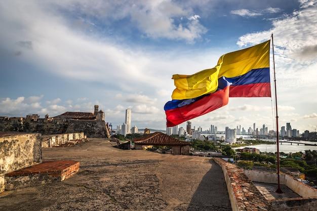 La bandiera colombiana nel forte di cartagena in una giornata nuvolosa e ventosa. cartagena, colombia