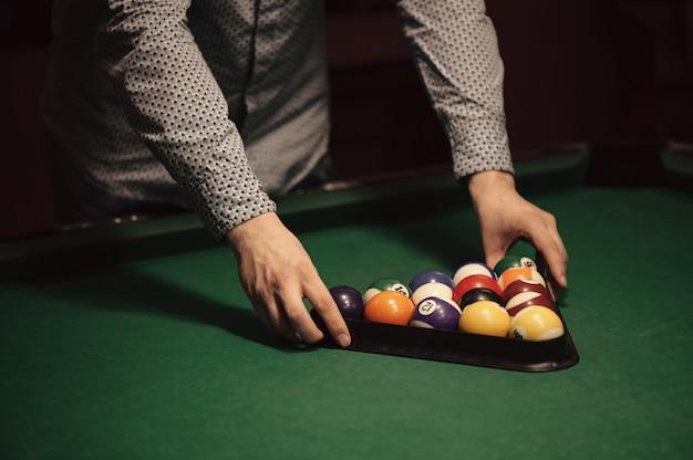 Palle di colore del biliardo americano nel triangolo sul tavolo da biliardo e primo piano del giocatore di biliardo