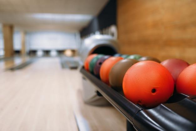 Palle da bowling colorate nell'alimentatore, corsia con perni, nessuno. concetto di gioco della ciotola