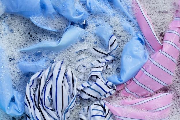 Gli indumenti colorati vengono immersi nella dissoluzione dell'acqua detergente in polvere. concetto di lavanderia