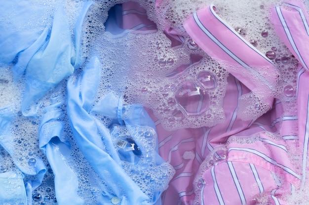 I vestiti colorati immergono nella dissoluzione dell'acqua detergente in polvere. concetto di lavanderia