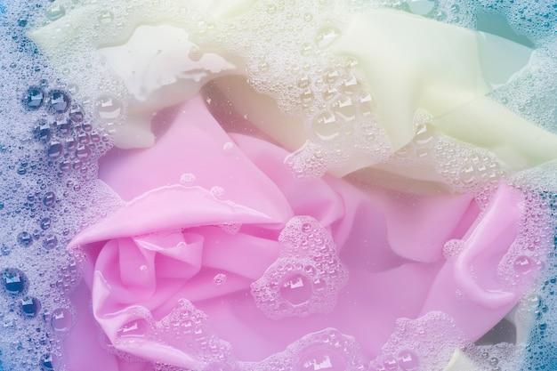 I vestiti colorati si immergono nella dissoluzione dell'acqua detergente in polvere. concetto di lavanderia