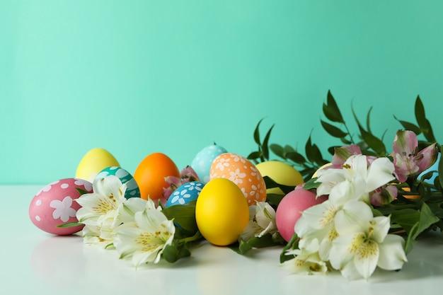 Colore uova di pasqua e fiori di alstroemeria su sfondo di menta