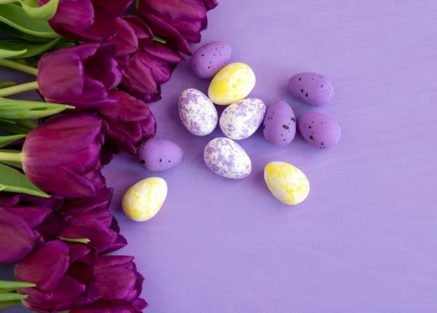 Colore uovo di pasqua e fiori viola tulipani su sfondo viola.