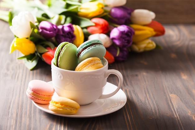 Amaretti colorati in una tazza e fiori sullo sfondo