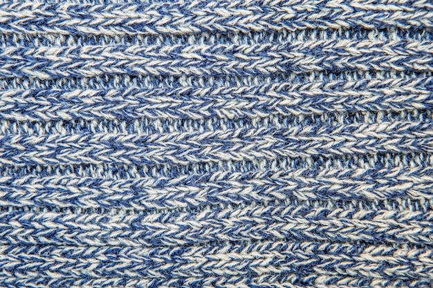 Maglione o sciarpa di filo intrecciato di colore melange come sfondo. trama di lana a coste