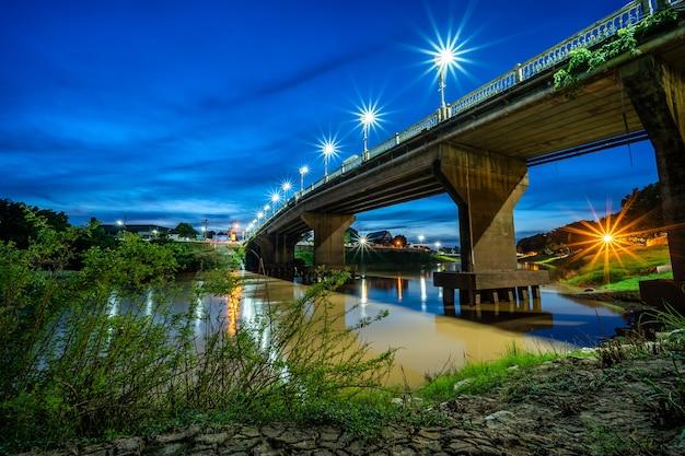 Il colore del semaforo notturno sulla strada sul ponte (eka thot sa root bridge) a phitsanulok, thailandia.