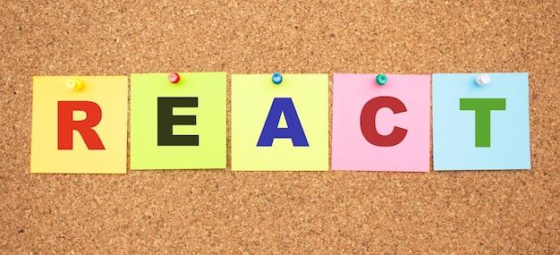 Note di colore con lettere appuntate su una tavola. parola react.