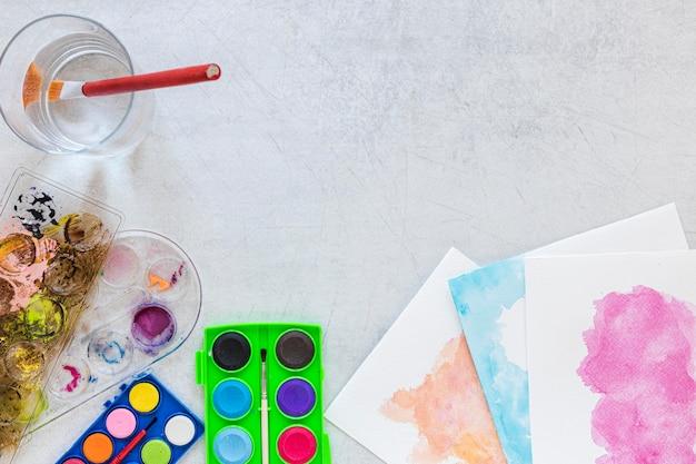 Tavolozza dei colori in scatola e bicchiere d'acqua
