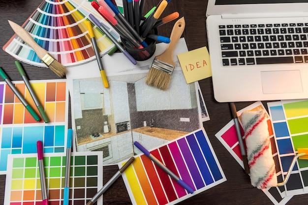 Tavolozza dei colori per la ristrutturazione della casa di design. schizzo di appartamenti con laptop campionatore e pennello alla scrivania. giornata di creatività