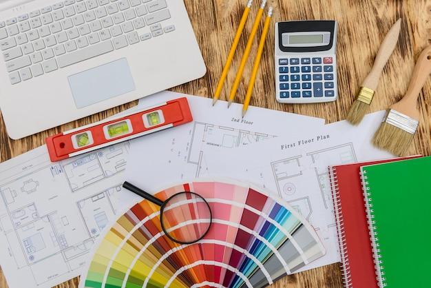 Tavolozza dei colori con strumenti di pittura, laptop e progetto di casa
