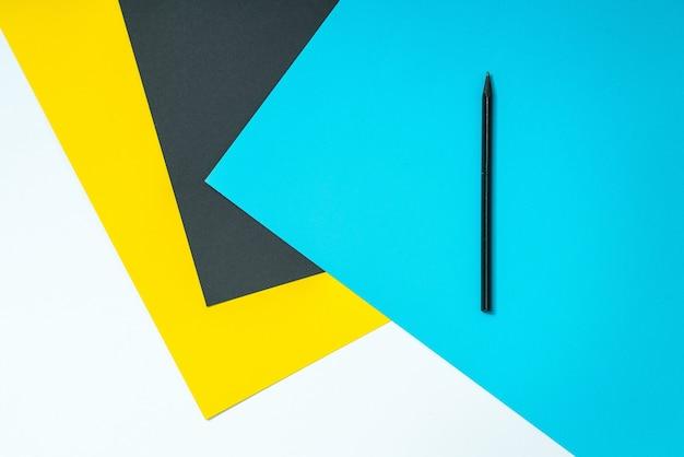 Carte a colori con penna nera in cima, materiale scolastico.