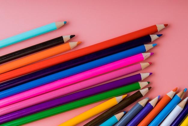 Colori la matita isolata su fondo rosa, concetto di arte di istruzione.