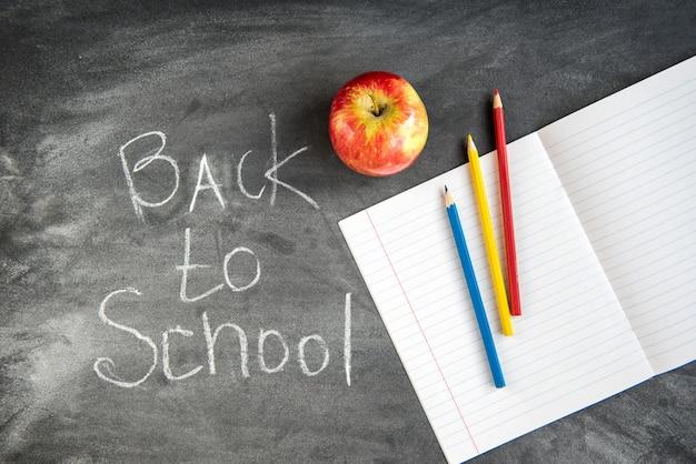 Matite colorate, quaderno su sfondo nero bordo. torna al concetto di scuola.