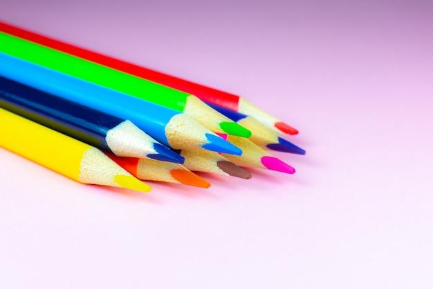Matite colorate che si trovano su sfondo rosa. avvicinamento. torna al concetto di scuola. studio dell'arte colorata e processo di pittura. disegnare con le matite. copia lo spazio per il desiderio della cartolina.