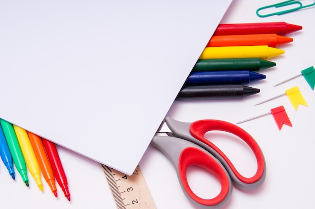 Matite colorate e acquerelli su bianco, torna a scuola, cancelleria con spazio vuoto