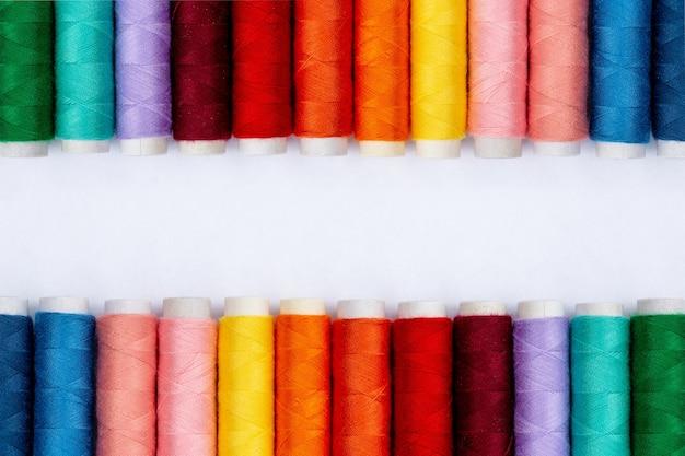 Filati per cucire di colore su sfondo bianco, vista dall'alto.
