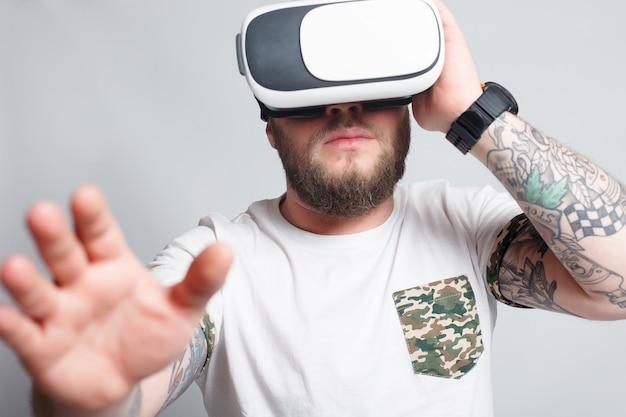 Ripresa a colori di un giovane che guarda attraverso una realtà virtuale, un dispositivo con cui è possibile sperimentare la realtà virtuale su un telefono cellulare. l'uomo tocca la mano. foto sfocate