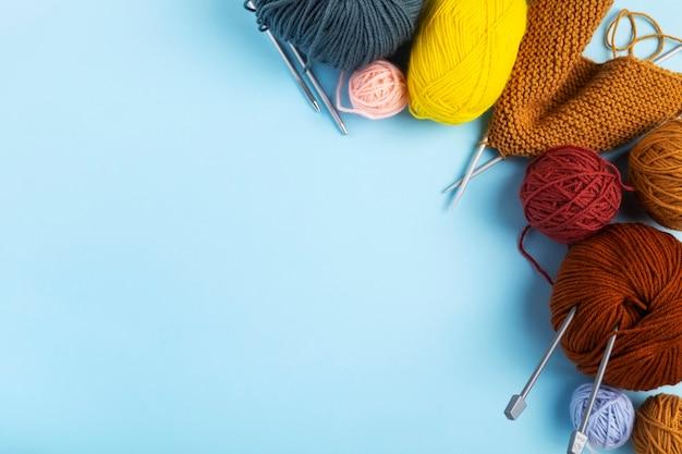Filati di colore per maglieria, sfondo blu. progetto di maglieria in corso. vista dall'alto. copia spazio