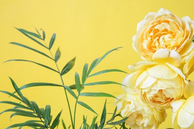 Colore anno 2021. festosa composizione di fiori rosa e piante tropicali su sfondo giallo.