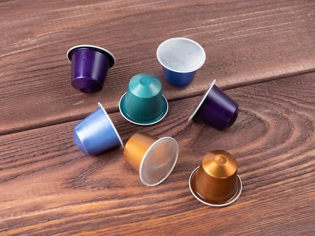Capsule in alluminio colorate con caffè macinato su fondo in legno. vista dall'alto, disposizione piatta, capsule per macchina da caffè