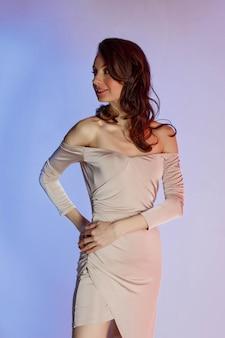 Sfondo colorato, luci al neon, girato in studio. ritratto di moda di una giovane donna bruna elegante.