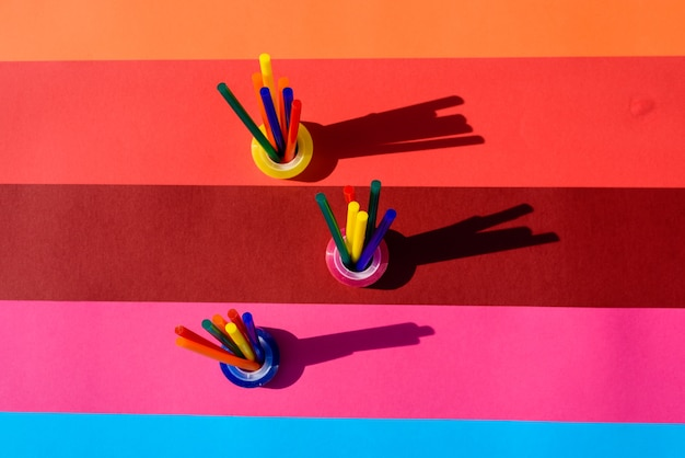 Sfondo colorato visto dall'alto con barrette di plastica da utilizzare in artigianato e cancelleria.