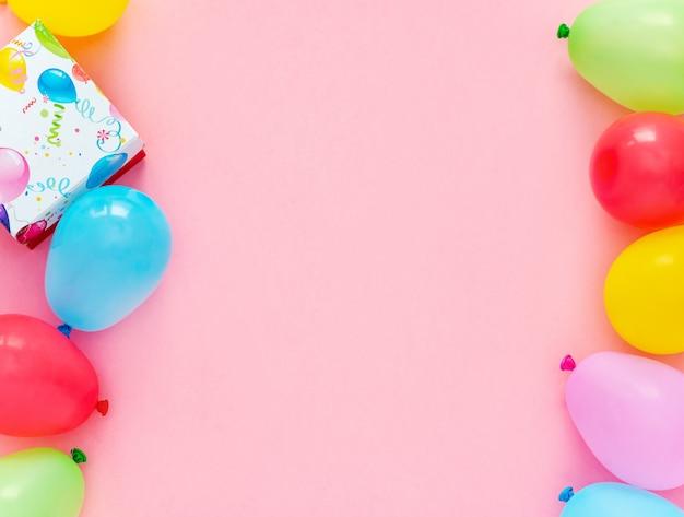Palloncini colorati e confezione regalo su uno sfondo rosa