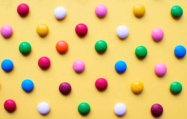Palline di zucchero colorate su una superficie gialla