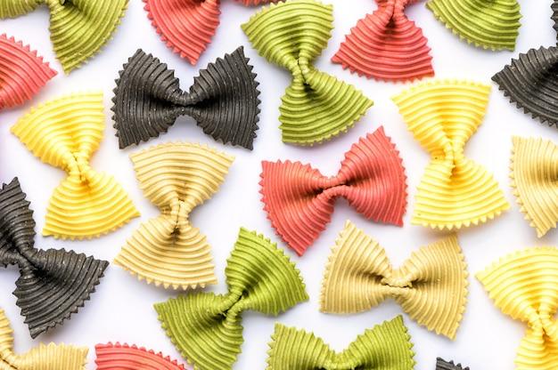Pasta con papillon colorato. farfalle multiple del primo piano isolate su fondo bianco.