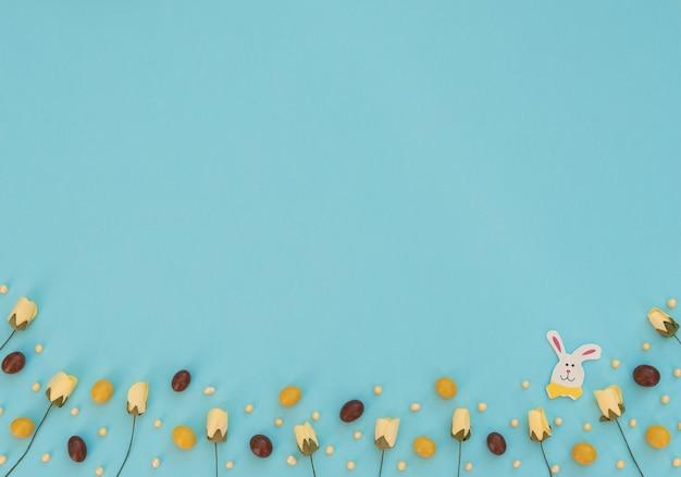 Uova di pasqua colorate di cioccolato marrone e giallo fiori primaverili e coniglietto di pasqua in legno