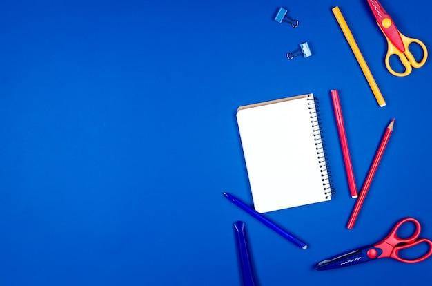 Forniture scolastiche differenti colorate su fondo di carta blu.