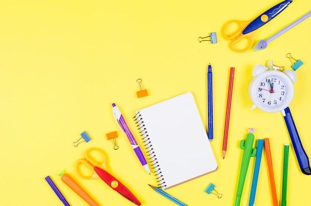 Forniture scolastiche diverse colorate su sfondo di carta gialla morbida.