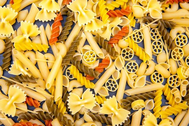 Diversi tipi di pasta italiana colorati su sfondo scuro