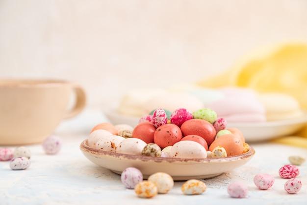 Dregees colorati con tazza di caffè sulla superficie di cemento bianco e tessuto giallo