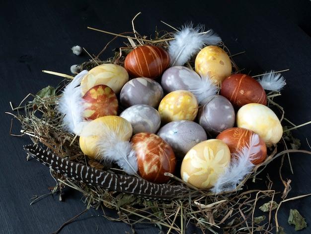 Le uova di pasqua colorate vengono poste su un nido di paglia e un tavolo di legno nero