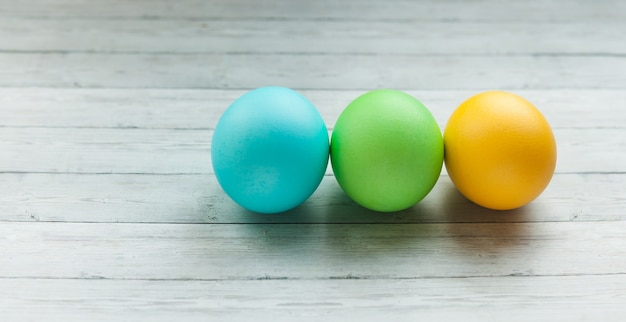 Uova di pasqua colorate su una superficie di legno chiara