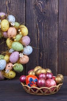 Uova di pasqua colorate. uova eterogenee di tiro verticale su fondo di legno rustico scuro.